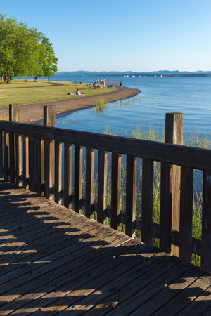 An old wooden walkway leads to a park by a lake Standard-Bild