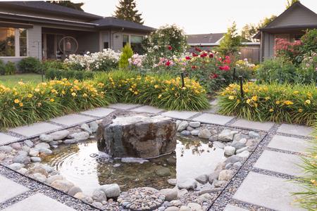 A meditative stone fountain hidden in a backyard garden. Standard-Bild