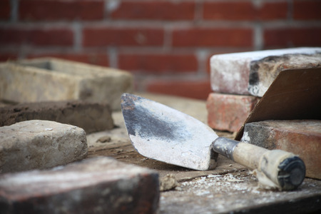 This photo depicts the work of a bricklayer. This bricklaying image includes a trowel, mold or cast, along with bricks. The job of laying bricks takes special skill.