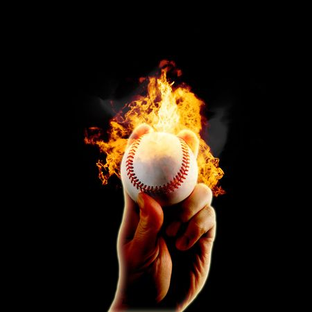Hand grips a baseball on fire isolated on black background. Imagens