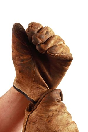 Person puts on a pair of worn work gloves, isolated on a white background. Imagens