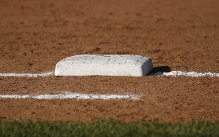 the field and in depth: Closeup of a base on a baseball field with shallow depth of field. Stock Photo
