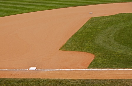 A portion of an baseball parks dirt and grass infield showing second and third bases.