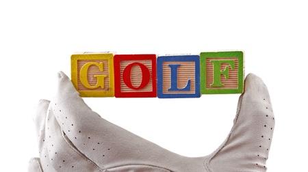 golf glove: Golf glove holds ABC baby blocks spelling  Stock Photo
