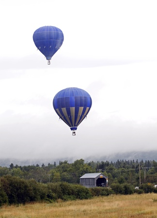 SUSSEX, CANADA - SEPTEMBER 9, 2011 - Two balloons fly over Plumweseep Covered Bridge at the Atlantic International Balloon Fiesta on September 9, 2011 in Sussex, Canada. Stock Photo - 10677854