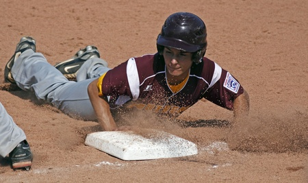 BANGOR, MAINE - AUGUST 18, 2011 - Kenny Rhodes of US Southeast (Palm Bay, Florida) slides safely back to first base at the Senior League Baseball World Series against Asia-Pacific (Tanauan City, Philippines) August 18, 2011 in Bangor, Maine.