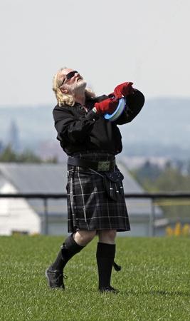 DIEPPE, CANADA - AUGUST 14, 2011 - Kilt-wearing Dave Nicholl of Scotland flies his kite in the 2011 Dieppe Kite International on August 14, 2011 in Dieppe, Canada.