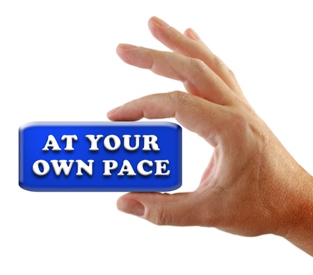 Closeup of a hand gripping a message At Your Own Pace, possibly for a business strategy, isolated on a white background. Imagens