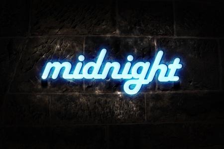 """ortseingangsschild: Blaue Neon-Schild an die Wand mit der Meldung """"Mitternacht""""."""