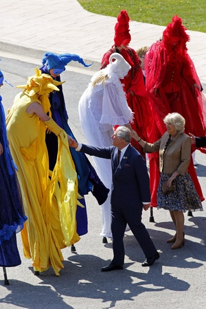 prince charles of england: Saint John, Canada - May 21 - Charles, Prince of Wales, and Camilla, Duchess of Cornwall, meet performers on stilts at the Marco Polo cruise terminal on May 21, 2012, in Saint John, Canada.