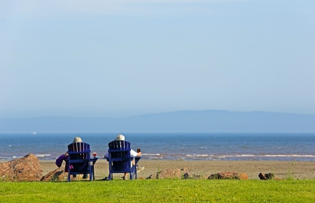 adirondack chair: Two people sit on blue Adirondack beach chairs overlooking the beach. Stock Photo