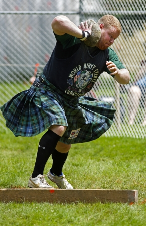 hammer throw: FREDERICTON, CANADA - July 28: Greg Hadley competes in the stone throw at the New Brunswick Highland Games Festival July 28, 2013 in Fredericton, Canada.