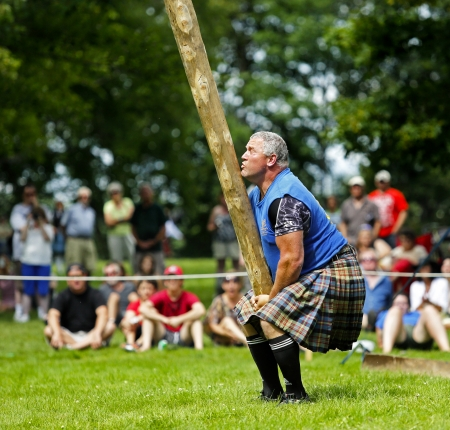 FREDERICTON, CANADA - July 28: Dirk Bishop tosses the caber at the New Brunswick Highland Games Festival July 28, 2013 in Fredericton, Canada.