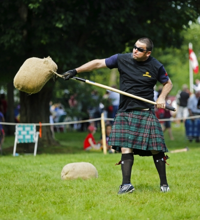 tosses: FREDERICTON, CANADA - July 28: Bryan MacLean tosses the sheaf at the New Brunswick Highland Games Festival July 28, 2013 in Fredericton, Canada.