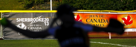 SHERBROOKE, CANADA - August 5: A womens softball pitcher is silhouetted against Canada Games signage August 5, 2013 in Sherbrooke, Canada.