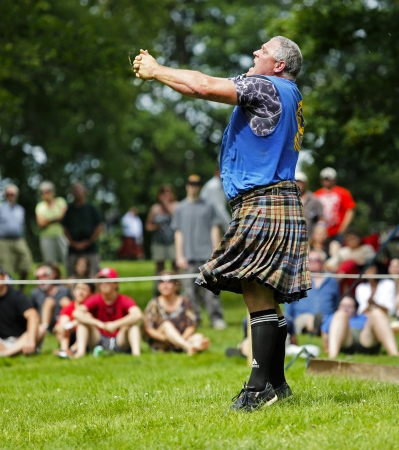 tosses: FREDERICTON, CANADA - July 28: Dirk Bishop tosses the caber at the New Brunswick Highland Games Festival July 28, 2013 in Fredericton, Canada.