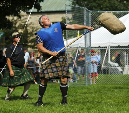 FREDERICTON, CANADA - July 28: Dirk Bishop tosses the sheaf at the New Brunswick Highland Games Festival July 28, 2013 in Fredericton, Canada.