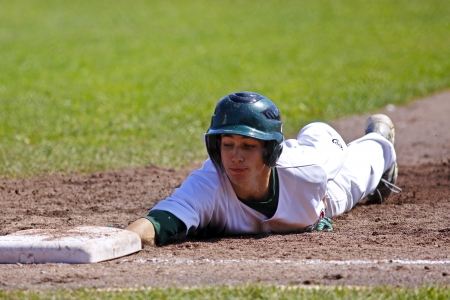 SHERBROOKE, CANADA - August 6: Shawn Bartley of New Brunswick slides back to first base in men's baseball at the Canada Games August 6, 2013 in Sherbrooke, Canada.