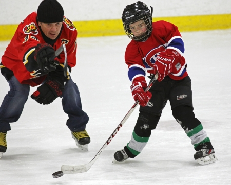 richer: Former National Hockey League star Theo Fleury helps a youngster with his passing skills at a hockey clinic in Sussex, New Brunswick, Canada, on Dec. 10, 2013. Fleury was in the province as part of an NHL Legends tour.