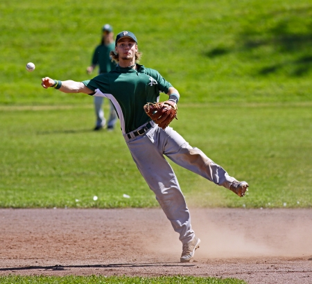 shortstop: SHERBROOKE, CANADA - August 6: Prince Edward Island shortstop Jay Oram throws to first base in mens baseball at the Canada Games August 6, 2013 in Sherbrooke, Canada.