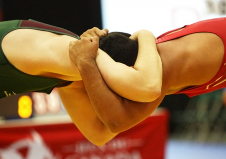 grasp: SHERBROOKE, CANADA - August 7: Two male wrestlers in a headlock at the Canada Games August 7, 2013 in Sherbrooke, Canada.