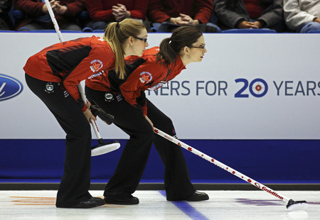 opponents: SAINT JOHN, CANADA - March 19: Alison Kreviazuk and Lisa Weagle of Canada follow an opponents shot at the Ford World Womens Curling Championship March 19, 2014 in Saint John, Canada.