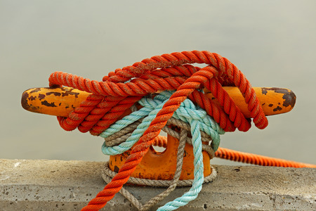 mooring: Mooring bollard with rope on pier by the sea.