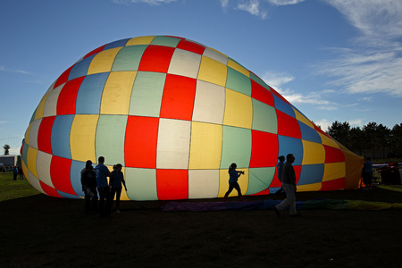 Silhouettes against an inflating hot air balloon during the evening launch at the 30th annual Atlantic International Balloon Fiesta in Sussex, New Brunswick, Canada, Sept. 12, 2015.