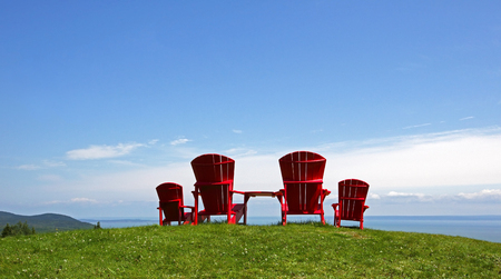 Four red Adirondack chairs on a grassy slope overlooking a body of water.