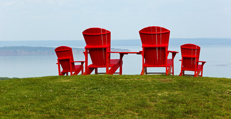 adirondack: Four red Adirondack chairs on a grassy slope overlooking a body of water.