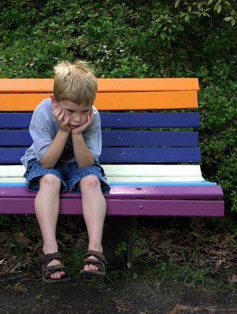 Een kleine jongen op een bankje zoekt vervelen. Stockfoto