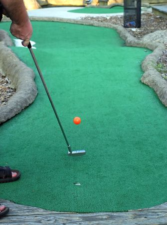 mini: A man putting a mini-golf ball.
