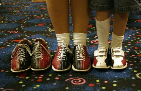 missing: Three pair of bowling shoes. Two being worn, one empty.