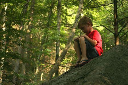 sulk: A little boy sitting on a big rock pouting.