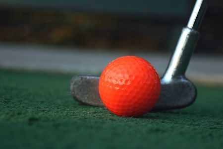 miniatures: A mini-golf ball and putter. Stock Photo