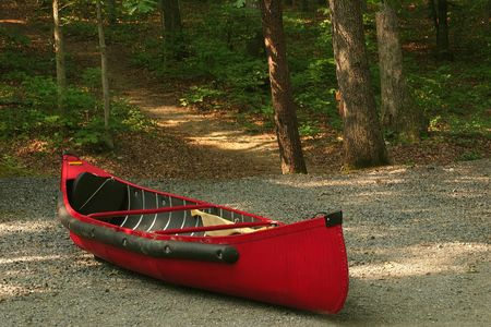 beached: A red canoe beached in the woods Stock Photo