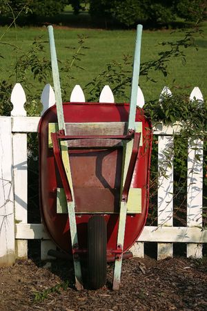 barrow: A red wheel barrow leaning against a white picket fence. Stock Photo