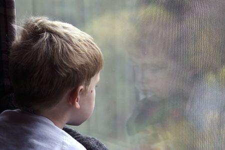 mirada triste: Un ni�o peque�o mirando por una ventana  Foto de archivo