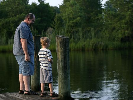 smirking: A father and son standing at the end of a pier.  The father is smirking at his son. Stock Photo