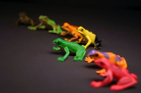 distinction: Toy frogs in a semi circle.  Selective depth, and postion make the green frog stand out from the rest. Stock Photo