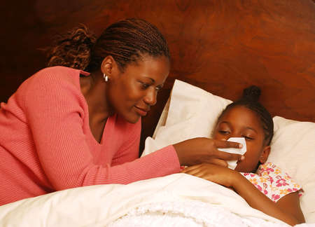 love blow: A mother helps her sick daughter blow her nose.