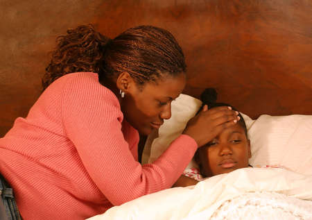A mother feels her daughters head for a fever.