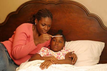 온도계를 읽는 아픈 아이와 어머니. 스톡 콘텐츠