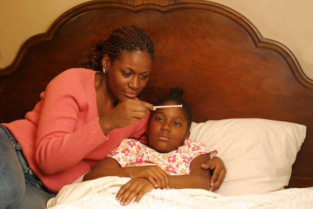 A mother with a sick child reading the thermometer.