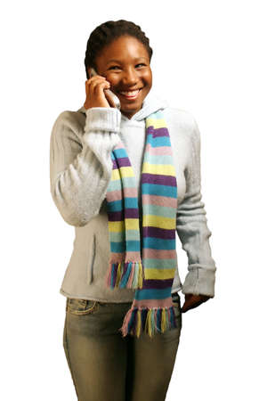 A teenage girl on a cell phone about to laugh. With clipping path. Фото со стока