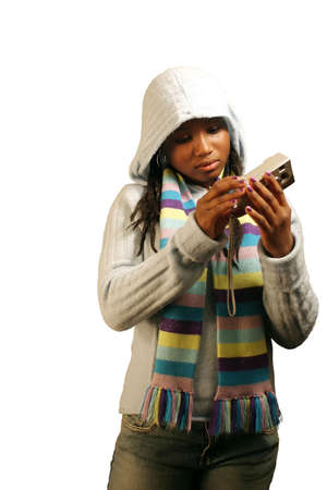 A teenage girl looking at photos on a digital camera.  Isolated with clipping path.