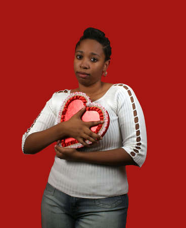 jilted: A young woman holding valentines gifts, looking depressed.