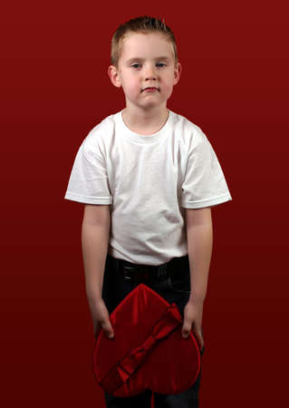 indifferent: A little boy holding a red heart.  Looks indifferent. Stock Photo