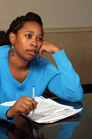 exemption: A young woman daydreaming while going over some forms.