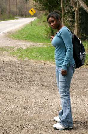 A teenage girl waiting for the school bus. photo